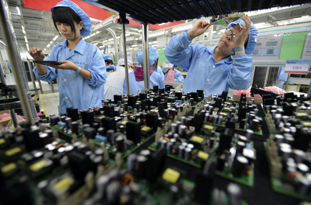 Employees work at a production line of electronic panels at a factory of FiberHome Technologies Group, in Wuhan